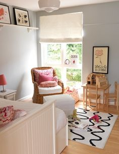 Adorable girl's bedroom design with blue gray walls paint color, wicker chair, schoolhouse pendant, white & black rug, pink damask pillows, white shelf and white trundle bed.