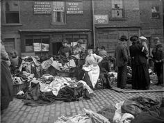 """""""A secondhand clothes seller at Newcastle cloth market reads as customers inspect her goods. A set of original glass negatives showing street scenes of century Newcastle found by Aaron Guy, who works at the city's Mining Institute. Victorian Street, Victorian London, Victorian Era, Victorian History, East End London, Old London, Old Pictures, Old Photos, Second Hand Clothes"""