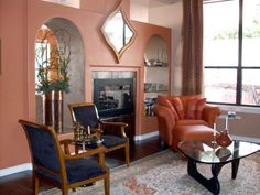 A terra cotta wall compliments the orange chair in this comfortable space to entertain.  http://www.schargelinteriors.com