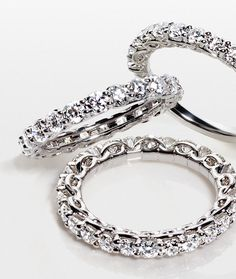 Elegantly timeless, these eternity rings feature round diamonds prong-set in platinum accentuated with an infinity motif in the profile.