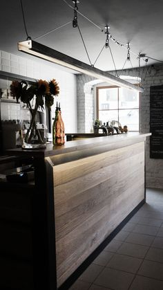 Bar of raw steel and oak wood with dedicated steel lamp. Troca Cafe and Lunch, Poznan. Poland