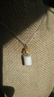 Your preserved breastmilk, solidified in a glass bottle pendant.
