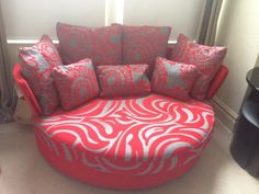 Loveseat, 175 cm x 130 cm in a mixture of plain and pattern reds.  May be purchased with either a static or a swivel base.