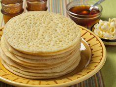 Dans un saladier, mettre eau, lait tiède, œufs, levure et semoule. Bien mélanger le tout pour obtenir une pâte liquide mais onctueuse