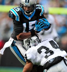 CHARLOTTE, NC - DECEMBER 23: Joe Adams #15 of the Carolina Panthers makes a catch as Mike Mitchell #34 of the Oakland Raiders defends during play at Bank of America Stadium on December 23, 2012 in Charlotte, North Carolina. (Photo by Grant Halverson/Getty Images)