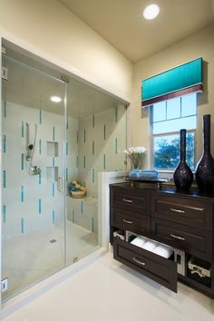 Style abounds in this Asian-inspired bathroom in shades of turquoise and brown. White tile with turquoise accents makes a unique and stunning statement in the shower, while the dark brown vanity and turquoise and brown cornice at the window add drama and depth to the space.