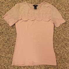 Pink H&M top Fancy t-shirt from H&M. Shoulders are a mesh-like material with pretty flower stitching and scalloped short sleeves. Very stretchy size small. H&M Tops Tees - Short Sleeve