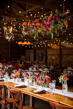 A colorful floral chandelier filled with orange roses, purple dahlias, and assorted daisies for a barn wedding | Brides.com