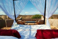 At Ol Donyo Wuas, there's a permanent bower on the roof deck above every suite that can be done up with fresh soft cotton linens, blankets, and hot water bottles. By moonlight, the savanna below is visible, as is Mount Kilimanjaro in the distance. The lodge, which sits on a ridge 50 feet above the plains, is surrounded by three water holes, and at night you can hear elephants sloshing around. When the moon is new, the sky is black and the heavens are so close that satellites and shooting…
