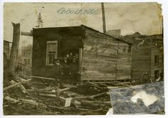 A photograph of five men standing in the doorway of a tarpaper shack in 1904.
