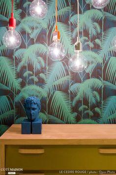 Un joli papier peint jungle rehaussé par des ampoules nues de couleur