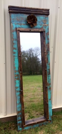 A gorgeous signature piece that will be center of attention in your entry, bedroom, bathroom  Wood Stain splashed with turquoise and distressed, this piece is handmade in Texas.  It features a top crown that is embellished with distressed nail heads and topped with a large rustic flower.  Mirrors on display are located in Huntsville, Nac and College Station boutiques as well as main warehouse. This piece can be made in other colors as well such as red, black, mint, pink, turquoise, dark wood…