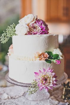 A two-tier buttercream wedding cake with flowers | @evynnlevalley | Brides.com