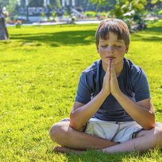 Young boy meditating on grass