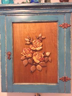 Our barn yard find old cabinet. It was distressed in teal and ebony then the panel was treated to a hand shaped rose bunch. Cedar and walnut were used for flower petals and stem.