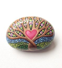 Hand painted river rock, painted beach stone. Tree of Life art stone, the stone is a lovely oval shape that fits perfectly in the palm of your hand. The branches are filled with bright flower blossoms and chartreuse green leaves. The sky and the rolling hills have been filled with hundreds of carefully placed dots. The periwinkle, sky blue dots create a bright gradient blue sky background. The rolling hills are filled with varying shades of green dots. The two tree trunks are intertwined…