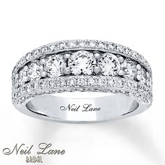 A row of bold round diamonds sparkle through the center of this glamorous anniversary band from Neil Lane Bridal®. Shimmering diamonds edge the band, for a total diamond weight of 2 3/8 carats. The 14K white gold ring features Neil Lane's signature inside the band. Diamond Total Carat Weight may range from 2.45 - 2.57 carats.