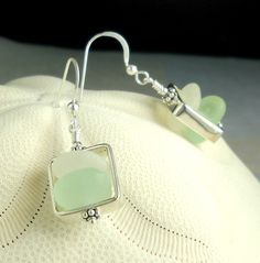 """Pretty new earring design in genuine sea glass set in Sterling Silver squares !I love aqua sea glass. It's such a special color to find and looks beautiful in any design. I found these lovely pieces as well as the perfect white gems in Northern California last year. They are cradled in these beautiful Sterling silver square cages. Each has been hand wire-wrapped in all Sterling Silver. Each square hangs from .925 Sterling Silver earring hooks and measures 1/2"""" by 1 1/2""""..."""