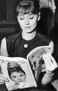 Amused Audrey Hepburn looks inside a Japanese magazine (featuring her on the cover) on the set of The Children's Hour in France, 1962.