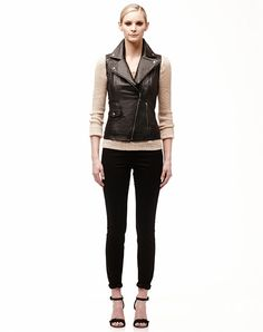 Soft leather slim fit vest with asymmetrical zipper front closure and snaps at collar and lapel.