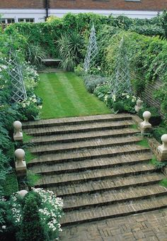 Anthony Noel garden in Bunny Williams Garden - brick steps lead to grass path lined with trellised obelisks