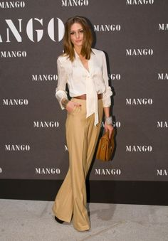 Olivia Palermo in a cream colored tie blouse with camel colored wide legged pants