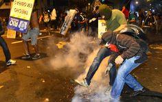 Manifestante chuta bomba de gás lançada pela polícia durante protesto no entorno do Maracanã. 30/06/2013.