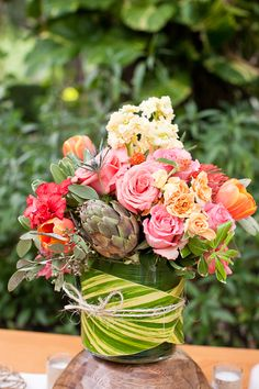Colourful arrangement with a large leaf & twine wrapped around the vase