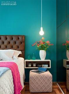 A cor da parede do quarto também é linda, com um criado mudo suspenso ótimo para ambientes pequenos, detalhe que permitiu com que o pufe ficasse ali.
