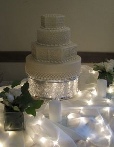 4 Tiered stacked cake with alternating round and hexagon tiers. Each tier features a different yet complimentary style of decorating.