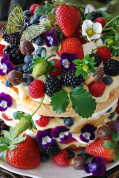 An angel food cake, cut in thirds, layered with lemon curd, whipped cream, berries & chocolate mushrooms