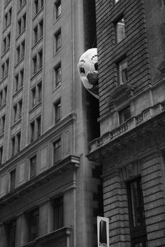 """I see you"" ~♛  Photo of weid black and white clown head coming through two old buildings.  Creepy and awesome."
