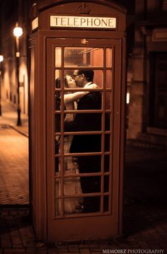 Cute kisses in a phone booth. (Make it blue!)