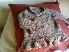seed stitch baby cardigan with ruffled trim. Pattern in Italian.