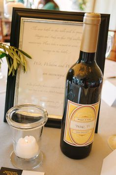Mark each table with a bottle of wine. Ask the guests at that table to sign a message on the bottle, and enjoy it on that number's anniversary!Photo Credit: William Walker Photography