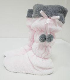Пухкави пантофи в бледо розово и сиво.Пухкави пантофи изработени от Софт в бледо розов цвят и в горната част със сиво. Отстрани се спускат сиви помпони със сатенена панделка. Пантофките са с височина до прасеца, като на няколко места са набрани и това не позволява да се смъкват.