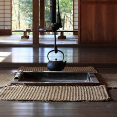 Wrought-iron kettle on an open fire in a traditional Japanese house