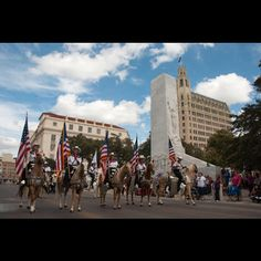 "The Alamo Cenotaph, The lead riders in a Veterans Day parade in San Antonio move past the Alamo Cenotaph, decorated on the side by sculptures of the Alamo defenders and on the front by a figure called ""the Spirit of Sacrifice."" Credit: James Southers/Alamy"