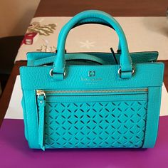 Kate Spade Mini Romy Handbag Gorgeous Kate Spade Handbag in color perri lane (teal) perfect for any occasion. Bag has one interior zipped pocket as well as two open interior pockets. The Kate Spade logo is embossed in gold in the feont as shown in 1st photo. Purchased for over 275.00 with taxes.   Make me an offer I cant refuse! kate spade Bags
