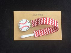 Cheer on your favorite baseball team with this adorable baseball pacifier clip!