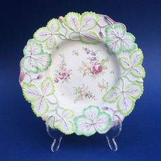 A Rare 18th Century Porcelain Longton Hall Strawberry Dish, the border moulded in leaves with alternating shades of pale and a darker green, purple tendrils and three wild strawberries picked out in pale red with gilded seeds, the centre painted in the 'Trembly Rose' style with three loose bouquets of flowers including a pink rose and scattered sprigs of yellow, purple and green