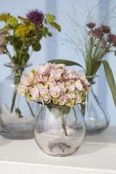 Små glassvaser med avskårne blomster er lekkert på festbordet.