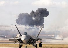 """The Pearl Harbor reenactment of """"Tora! Tora! Tora!"""" fills the sky with smoke as a Japanese Zero streaks by behind an F-22 Raptor during AirFest 2008 at Lackland Air Force Base Texas. [2.100px  1.500px]"""