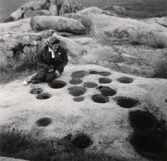 Photograph of a woman at bedrock mortars near Bakersfield, California, taken for the Archaeological Survey Association, mid-1900s. Subjects: Bakersfield, CA, bedrock mortars, California Indians, women