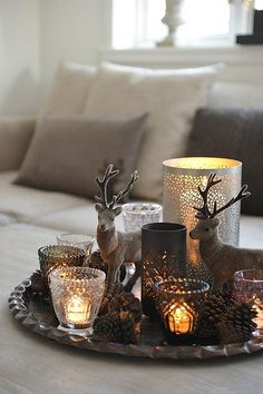 Lovely tablescape of reindeer & decorative candle holders in colors that recall the winter woods in snowfall.