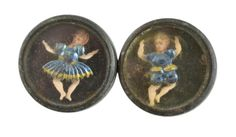A pair of antique jiggler metal buttons.