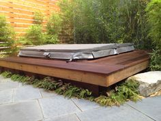 Hot tub zone with hovering Ipe' bench / deck and reclaimed Granite step by Sculpt Gardens San Franciso