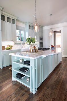 """An elegant marble counter tops mint green cabinetry to create a welcoming space to gather in this Craftsman-style kitchen. """"We wanted it to be a little something special,"""" designer Jamie House says. """"It's a walkway, so there wasn't enough room to extend the counter far enough to accommodate seating, but it's a good space to stop and talk."""""""