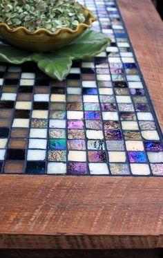 Mira qué sofisticada puede verse la mesa de tu jardín usando un diseño de mosaicos azules y violáceos.