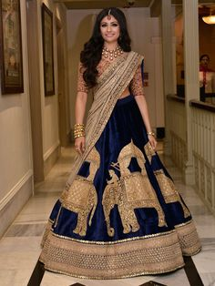 A Blue velvet Lehenga with a Pink Choli with zardosi work and a beige Dupatta by Sabyasachi for the Reception of Real Bride Devangi Nishar of WeddingSutra. More